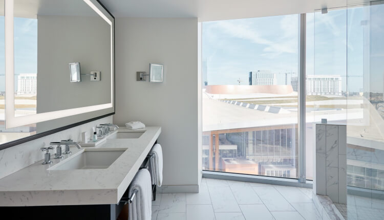 double sink vanity in spacious bathroom with floor to ceiling window