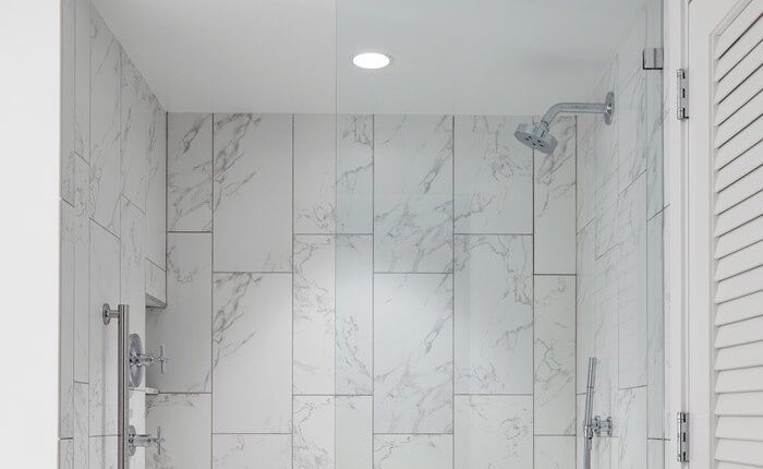 large marble walk-in shower with clear door