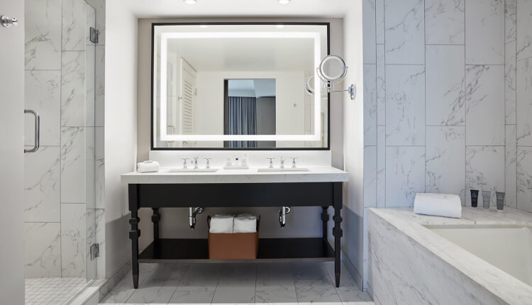 double sink vanity with lit up mirror between walk in shower and bathtub