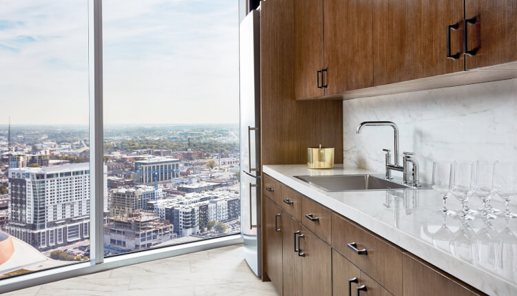 kitchenette with sink and fridge near floor to ceiling window with skyline view