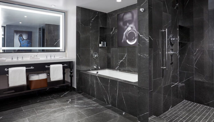 double sink vanity with lit-up mirror and black marble walls in tub