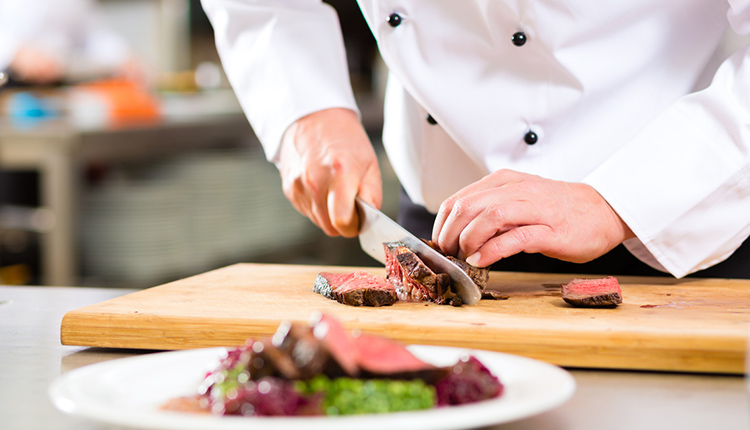 Close up of chef cutting tender steak on cutting board