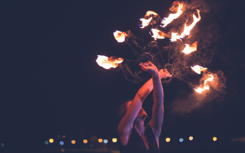 female circus flame tamer with live batons