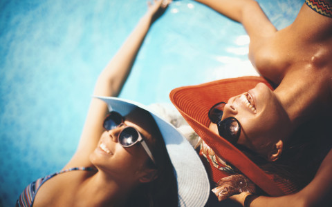 two women with hats lounging on the edge of the pool
