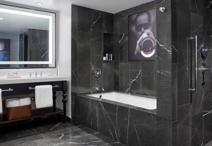 black marble bathroom with tub and lighted mirror