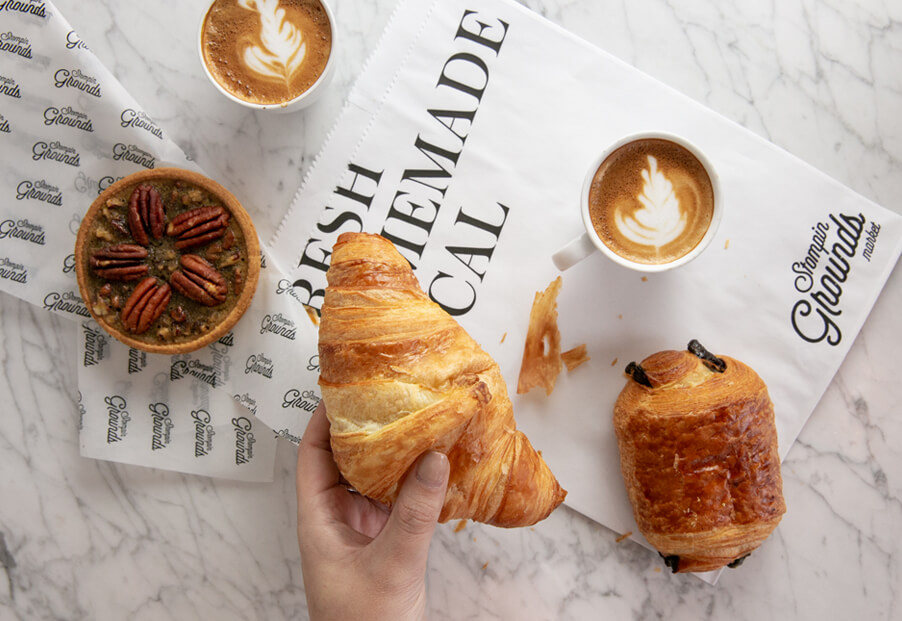 hand holding croissant over table that has coffee and other pastries on it