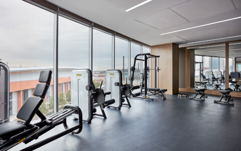 weight machines near floor to ceiling window and mirrors
