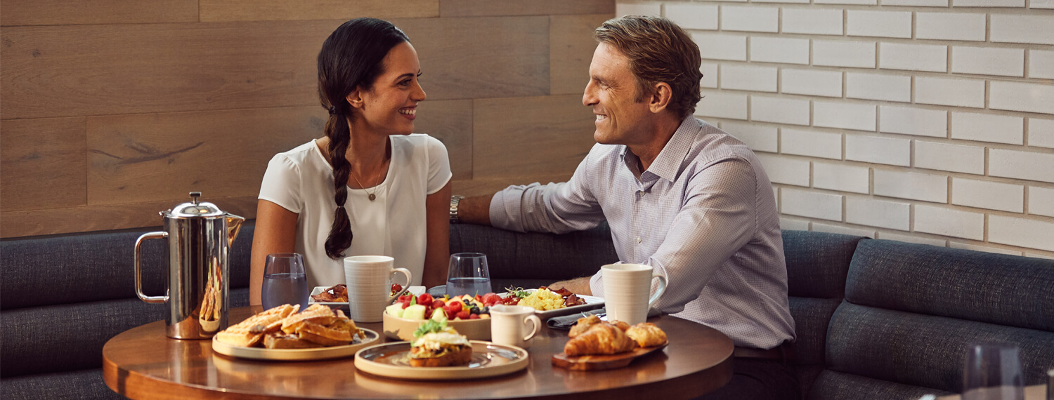 man and woman in booth with breakfast on the table