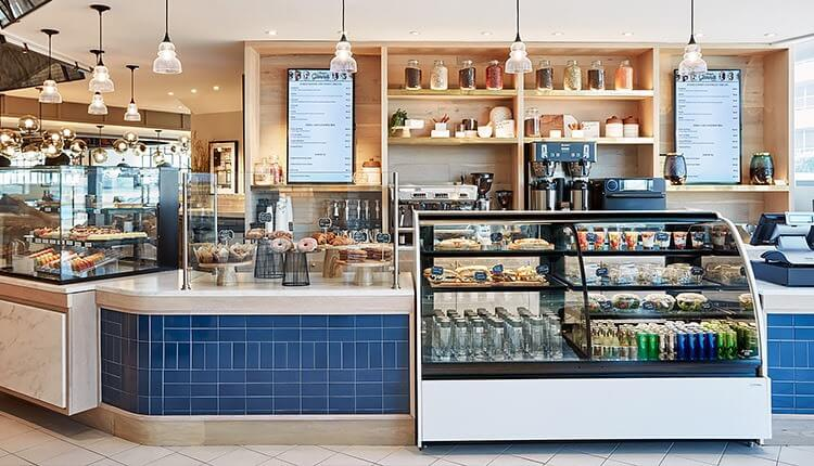 counter and display cases with pastries, salads, and sandwiches