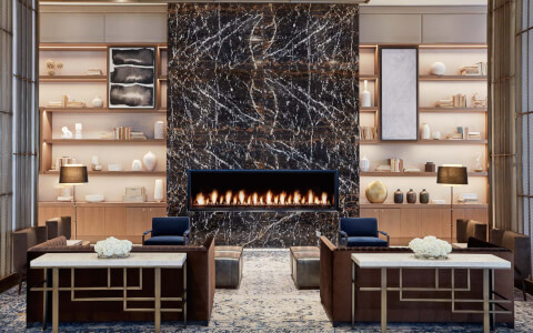 common seating area with fireplace built in a tall marble structure in between tall long shelves