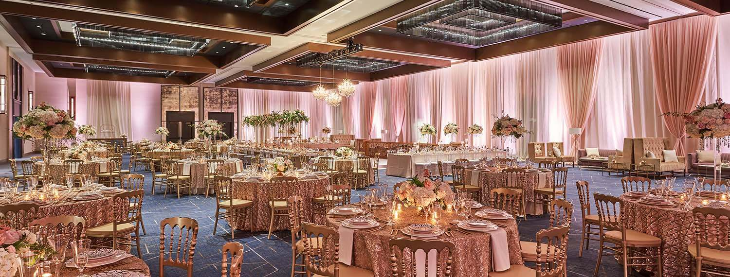 ballroom decorated for wedding with pink draping and tablecloths