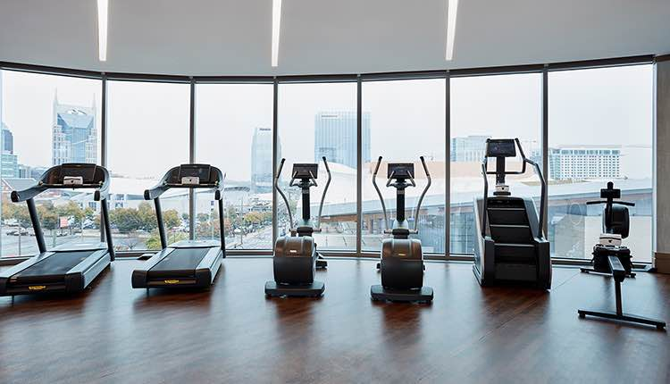 cardio gym machines lined up facing floor to ceiling window with view of nashville skyline