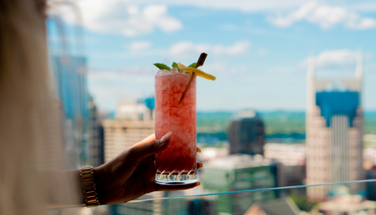 person holding cocktail over the glass railing overlooking the skyline