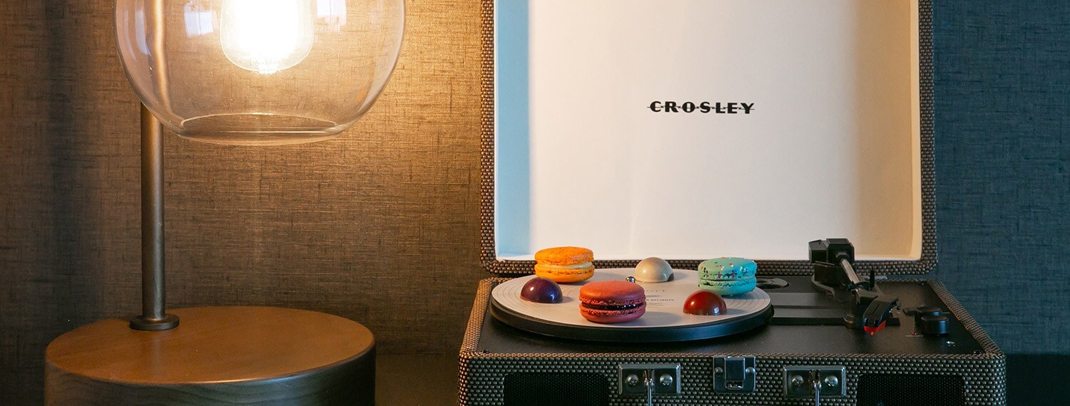 record player case display with desserts on a plate next to lamp
