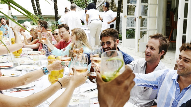 Group of friends sitting on large rectangular table as they toast