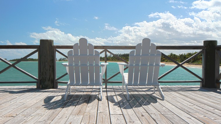 Two white wooden beach chairs overlooking blue ocean waters
