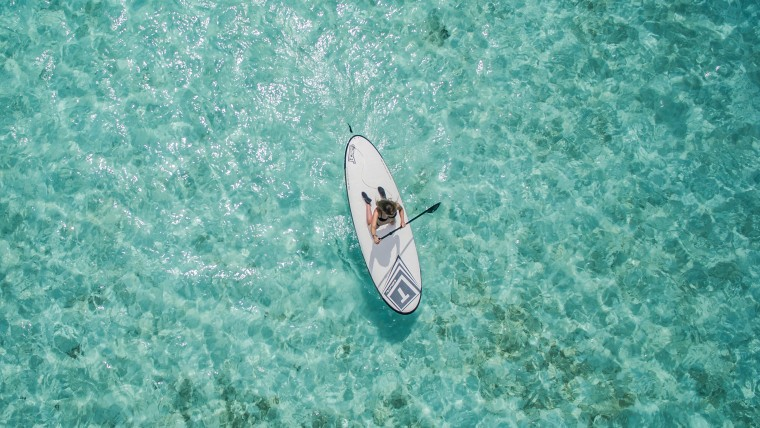 Aerial view of woman paddle boarding on clear blue waters
