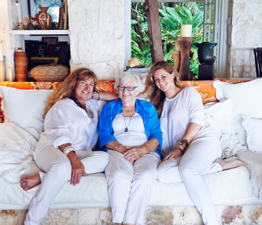 three women sitting on couch smiling