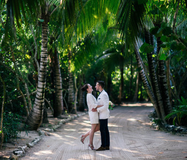 Bride and groom hugging by palm trees