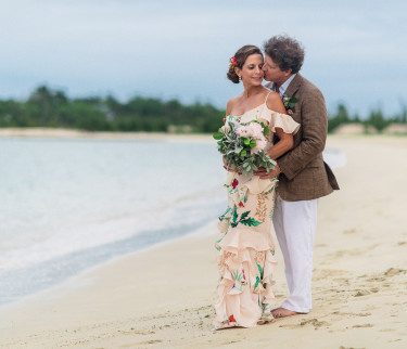 Groom and bride hugging by the shore