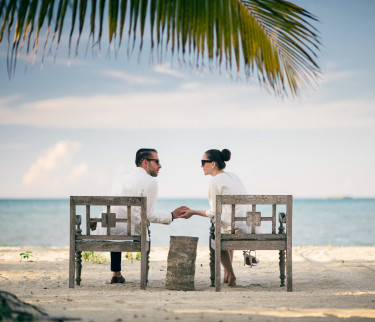 Couple sitting on the beach while holding hands