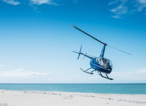 an image of a helicopter taking flight off the beach