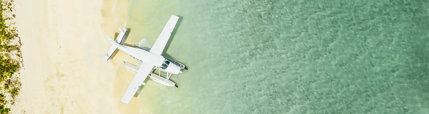 Header Sea Plane landing on a tropical island