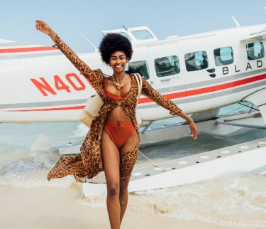 glamorous woman walking from a plane parked on the beach