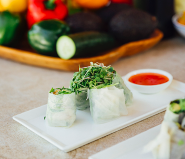 summer rolls on a white plate with sauce