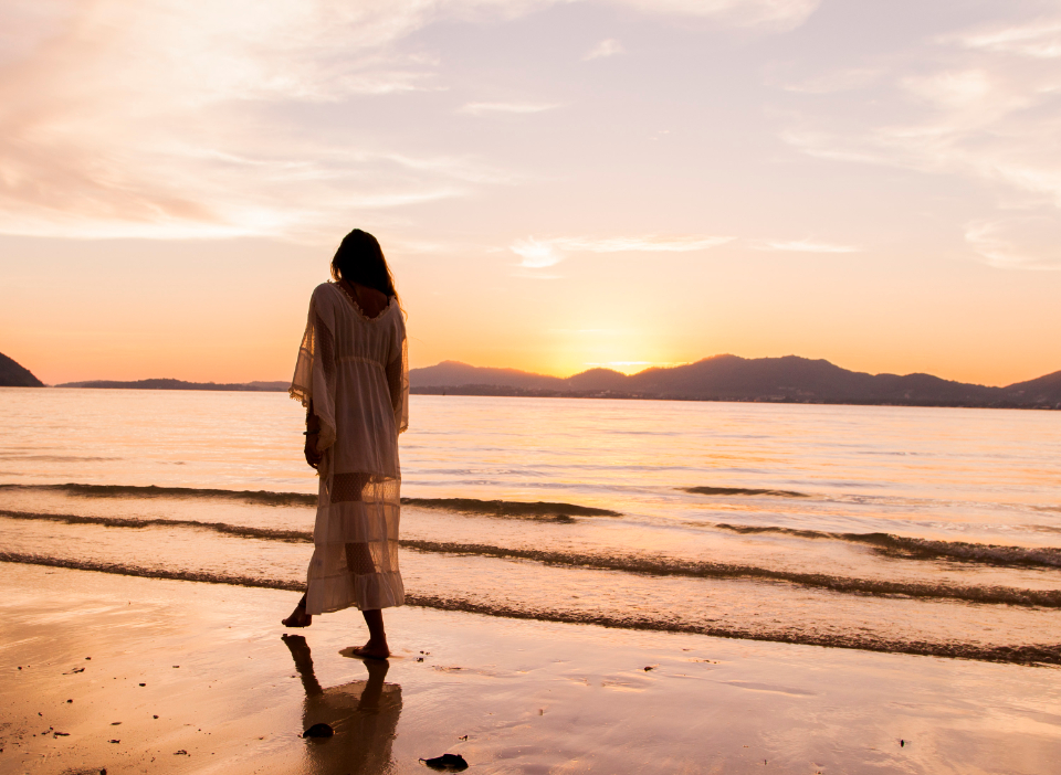 woman walking on beach at sunset