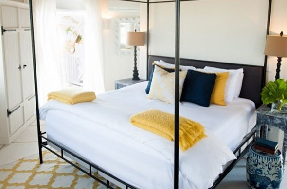 bedroom white bed with navy and yellow decor