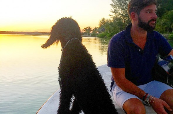 man and dog on a boat at sunset