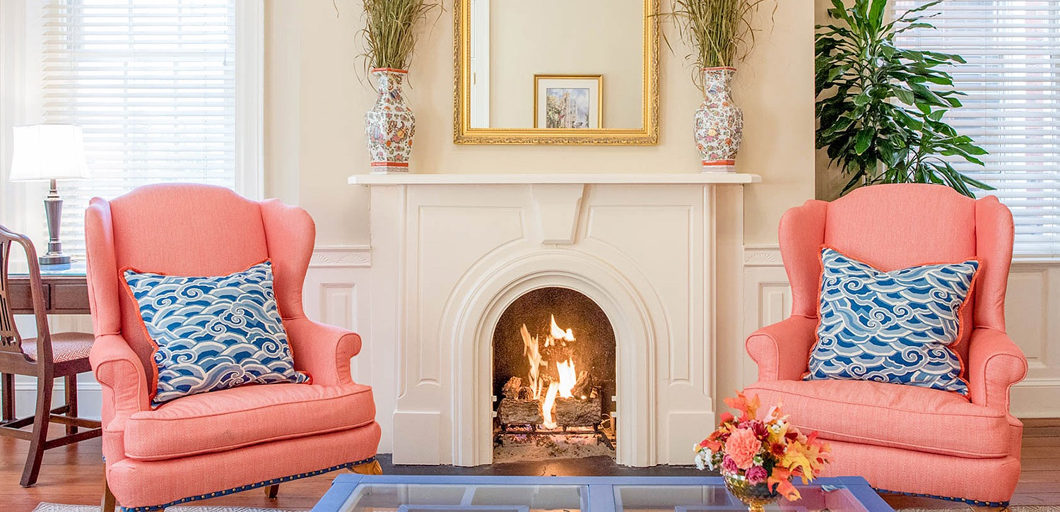 pink chairs and blue pillows in front of fireplace