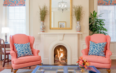 Peach padded chairs with blue patterned pillows next to glass coffee table & white fireplace