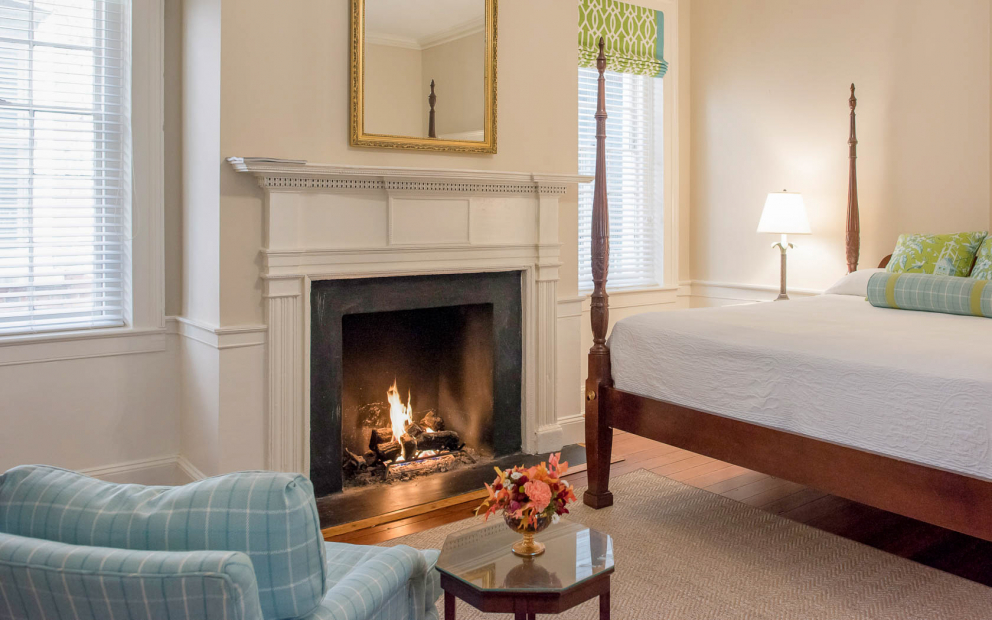 Room with king bed, striped blue couch next to glass table & lit up fireplace