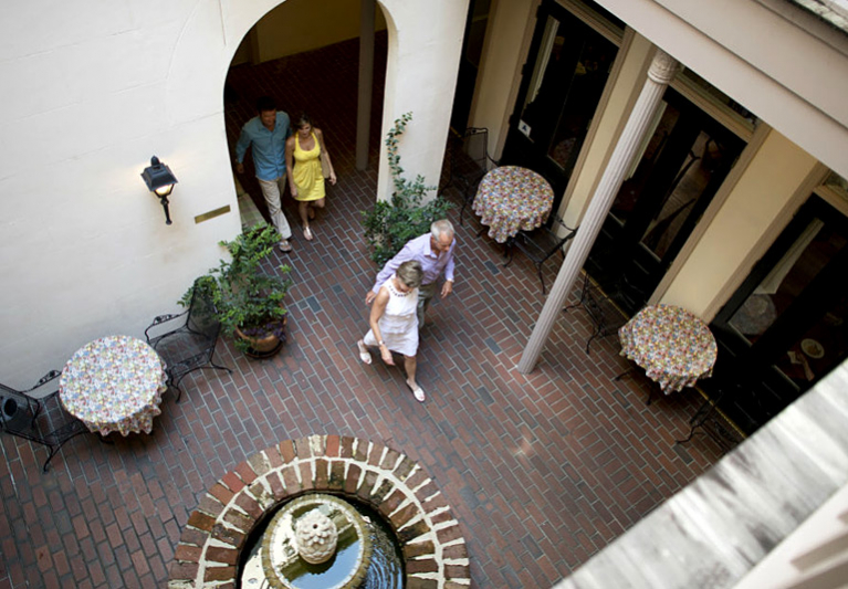 Aerial view of two couples walking through courtyard