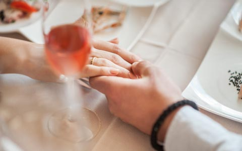 man holding a womans hand with a glass  of rose