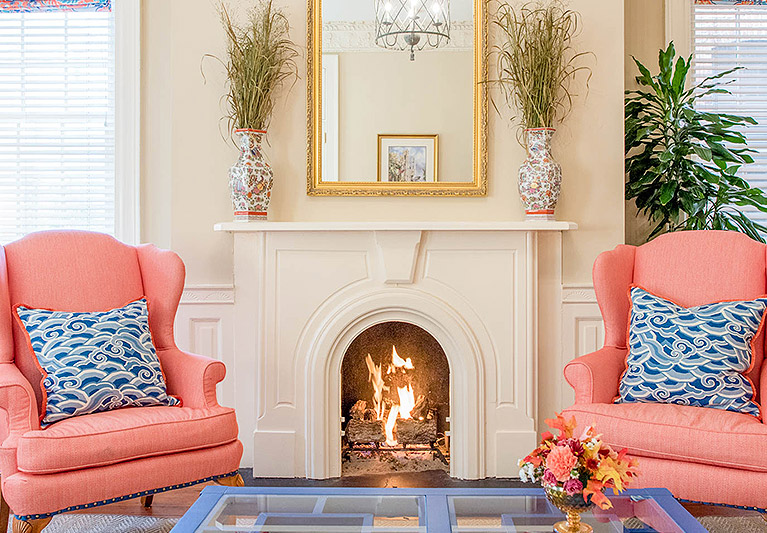 Peach couches with blue patterned pillows next to white lit up fireplace
