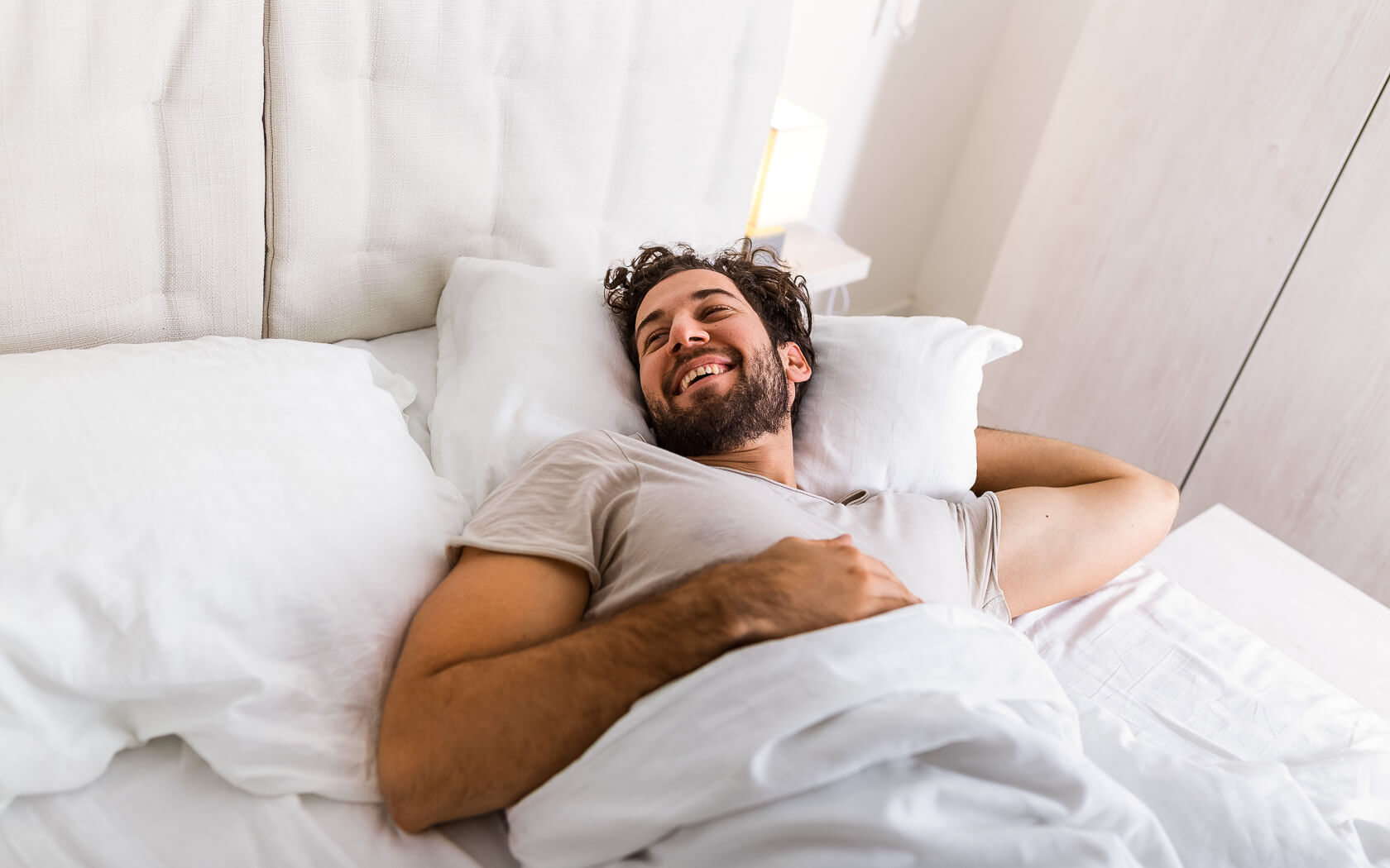 man laying in bed with comfortable linens