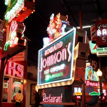 neon light signs at night in a downtown area
