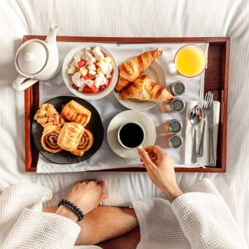 breakfast on a tray on top of a bed