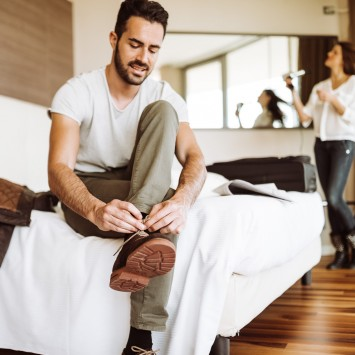 man sitting on edge of bed tying his shoes