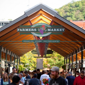 Farmers market sign on a pavilion filled with people