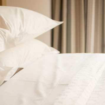 white pillows on a bed with white linens