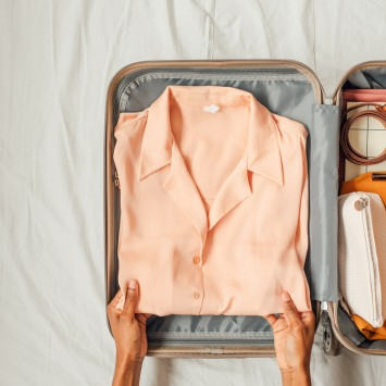 hands packing a peach colored shirt in a suitcase