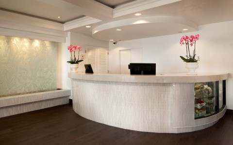 large white reception desk with pink flowers