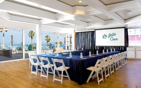 hotel event space prepared in a u shape in front of projection screen
