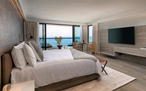 large king bed in room with flat screen tv and ocean view