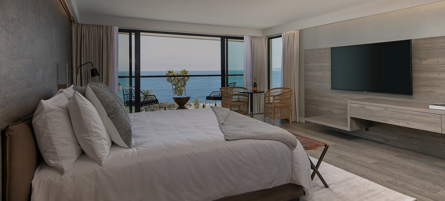 modern bedroom with large white bed with ocean view