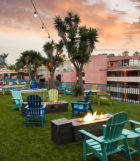 outside lawn with colorful chairs and fire pits during sunset